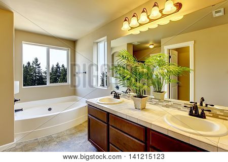 Bathroom interior in beige tones with modern brown vanity cabinet two sinks and large mirror bath tub and tile flooring. Northwest USA