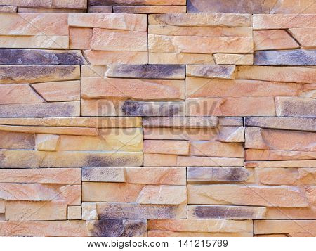 a wall from an artificial beige and gray stone facade with rough fractured surfaces