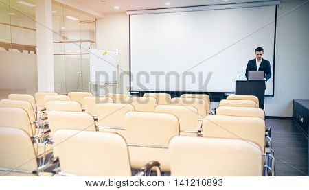 Serious handsome speaker preparing for the conference using laptop in empty boardroom
