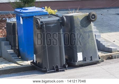 Dustbin with different colored lids for waste separation are upside down.