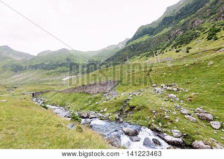 Photo of green capra peak a road and a small river in fagaras mountains Romania.