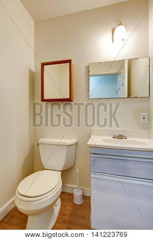 Simple Bathroom With Small Washbasin Cabinet And Mirror.