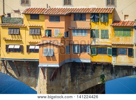 Beautiful traditional Italian houses on the bridge appear to be hanging over the Arno river.