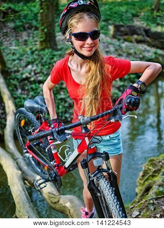 Girl with bicycle. Girl fording throught water . Bicycle trip is good for health. Bicycle girl wearing bicycle glasses.