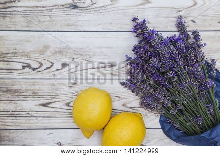 Bouquet of purple fresh fragrant lavender wrapped in blue paper with two fresh yellow lemons on wooden background