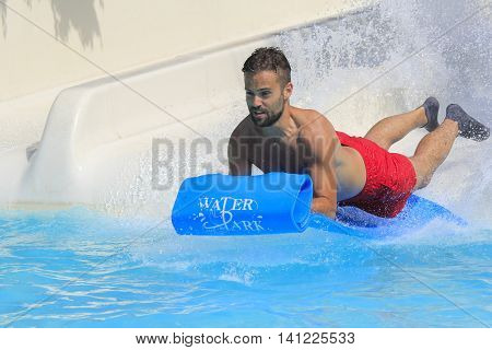 Rhodes Greece-August 1, 2016:Young men on the mat racer slide.Mat racer slide is very popular for young people in the Water Park.Water Water Park is located on the island of Rhodes in Greece and one of the most largest in Europe and is a very popular plac