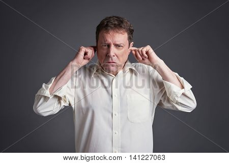 Middle age man covering his ears in the studio