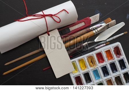Holiday art set of assorted watercolor paint, brushes, palette knife, paper cutter, a bundle of paper on black background