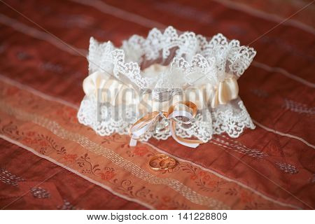 Decorated wedding garter with golden rings on red background. Marriage concept