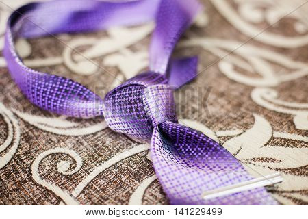 Purple necktie with trinity tie knot on a sofa close-up
