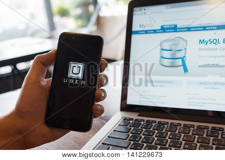 CHIANG MAI THAILAND - AUG 4 2016: man hand holding iPhone 6S with Uber app logo Uber engineering switched form PsotgreSQL to MySQL.
