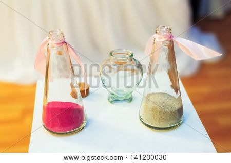 Sand ceremony on wedding glass vases for bride and groom. Marriage concept