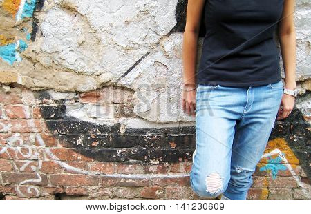 Cropped portrait of stylish young girl in casual clothes: black t-shirt and ripped jeans standing against colorful urban city brick wall background.