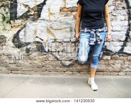 Portrait of stylish young girl in casual clothes: black t-shirt, plaid shirt and ripped jeans standing against colorful urban brick wall background.
