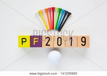 P.F.2019 - an inscription from children's wooden blocks and golf ball and wooden tees - Flat Lay Photography