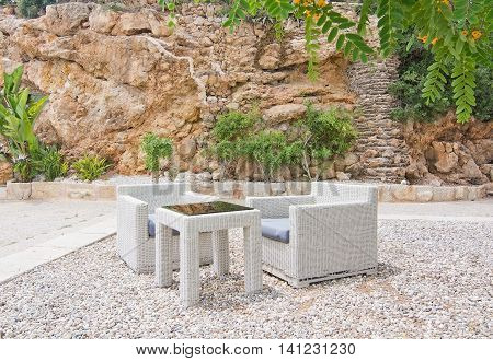 White rattan furniture in white gravel and tree with yellow flowers in Mallorca in June.