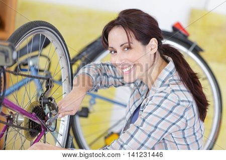 woman fixing a gear on bicycle
