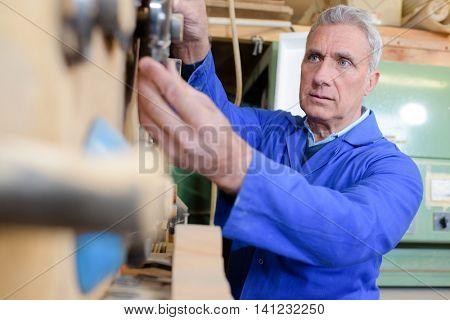 senior carpenter working at workshop