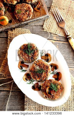 Fried mushroom burgers with onion and spices on a plate. Homemade mushroom cutlets. Delicious vegetarian and diet recipe. Top view