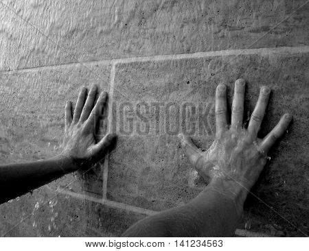 Water flows over the arms leaning against the water wall