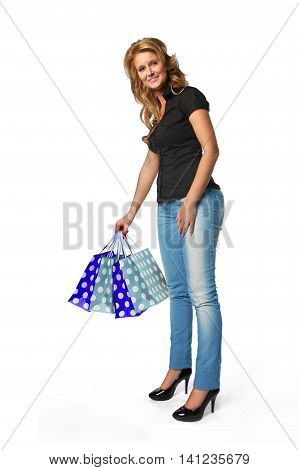 Attractive young woman holding shopping bags. Blonde and beaufitul in a white studio.