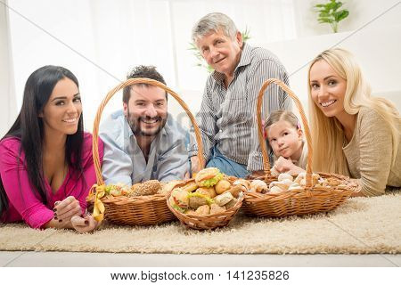 Happy family lying on a carpet in the living room around woven baskets filled with baked goods and looking at camera.