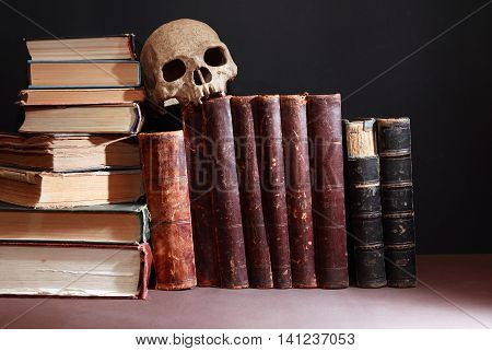 Vintage library. Human skull on old book in a row on dark background