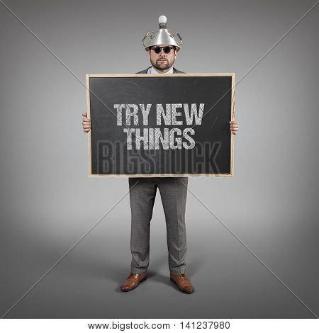 Try new things text on blackboard with science businessman holding blackboard sign