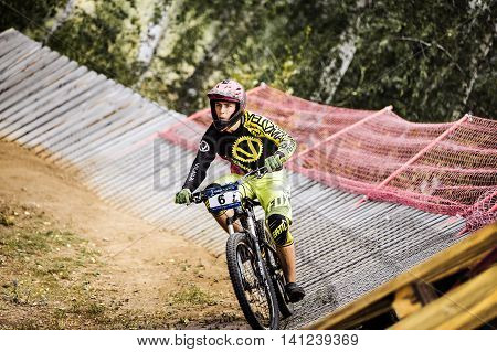 Magnitogorsk Russia - July 23 2016: athlete man extreme cyclist riding Insloped Turn during National championship downhill
