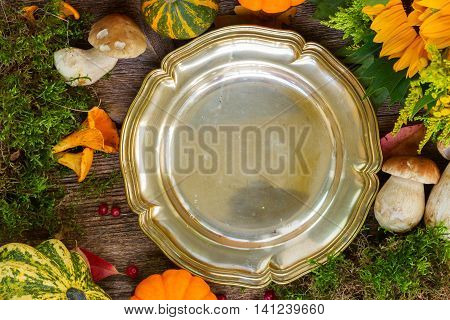 Empty plate with mushrooms, moss, leaves and pumkins frame on wooden table