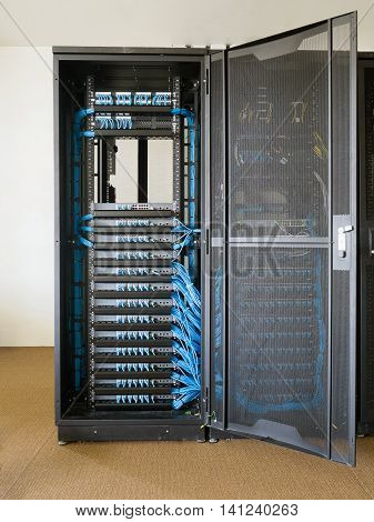 Network switch and ethernet cables in rack cabinet