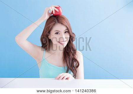 beauty woman holding apple on her head with isolated blue background asian