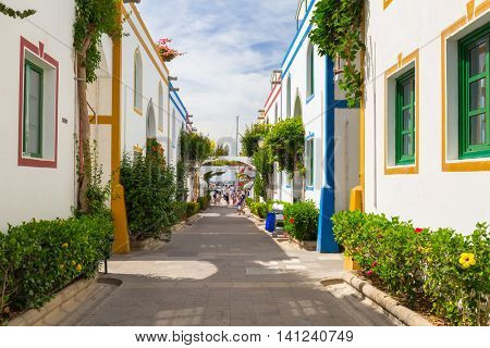PUERTO DE MOGAN, GRAN CANARIA, SPAIN - APRIL 21, 2016: Pedestrian alley in the harbor area of Puerto de Mogan, a small fishing port on Gran Canaria, Spain. It's called a Little Venice of the Canaries