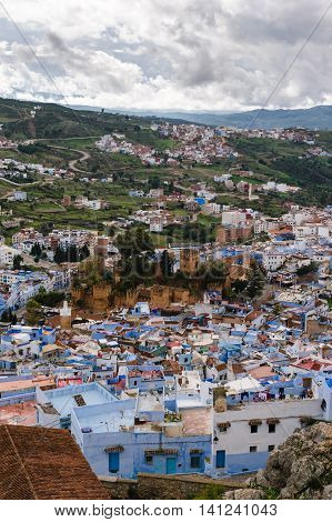 Awesome view over the blue painted city Chefchaouen in Morocco. In the middle you can see the historical Kashbah.  The sky is cloudy.