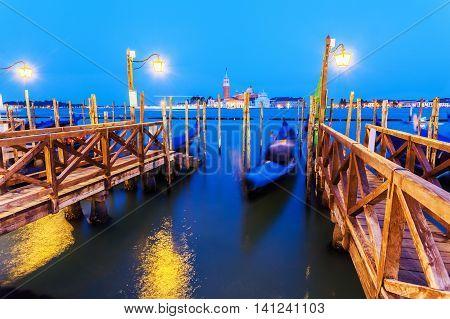 View of the Church of San Giorgio Maggiore and marina with gondolas at dusk. Venice. Travel Italy.