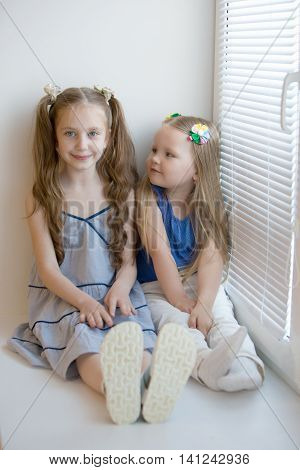 Two cute little girls sisters sitting on the window sill