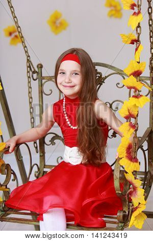 Close-up.Smiling little girl with long brown hair to her waist . Girl in bright red dress swinging on a swing