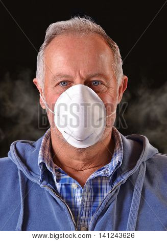 Man surrounded by smoke and air pollution wearing a safety protective mask portrait.