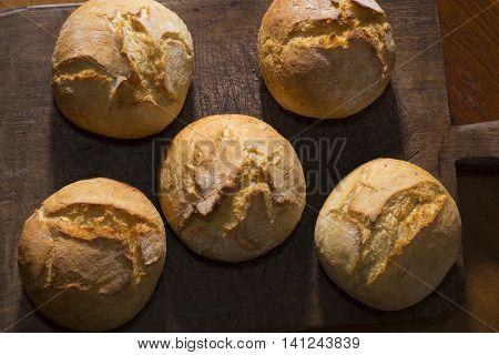 Traditional rustic bread rolls on a vintage cutting board