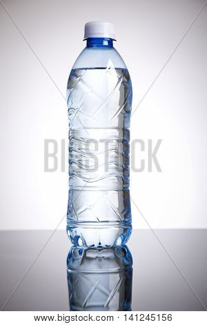 a bottle of water with gray background