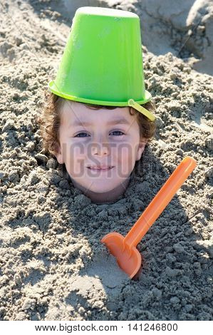 Small child buried in the sand of the beach