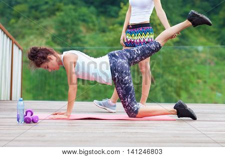 Personal trainer outdoor fitness exercise, young fit woman stretching. Back and buttocks workout