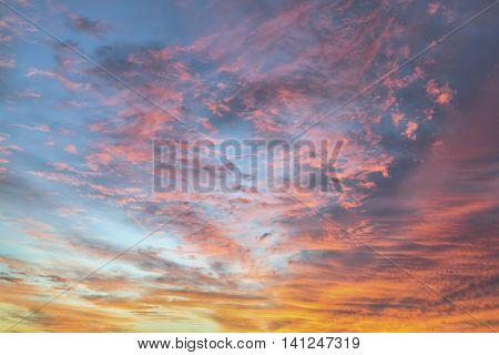 Gossamer clouds glow pink in a colorful sunrise sky.