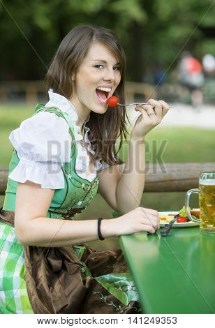 young bavarian woman in dirndl sitting outside with beer mug and eating
