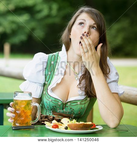 young woman in dirndl sitting in beer garden with food and beer and is yawning
