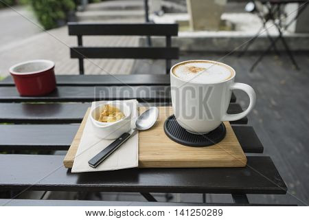 hot fresh coffee in white cup on black table on wooden tray biscuit cookie and silver spoon and white saucer cappuccino coffee mocha coffee espresso coffee latte coffee