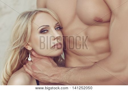Women's head pressed against the male body with big muscles.