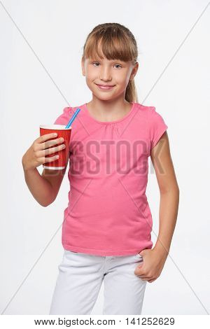 Little child girl holding a drink in disposable paper cup, isolated over gray background, with copy space