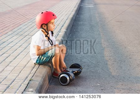 Boy Sitts With A Black Gyro Scooter Outdoors