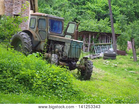 Smolensk, Russia - June 26, 2014: Old abandoned tractor stands on the deserted rural farmstead
